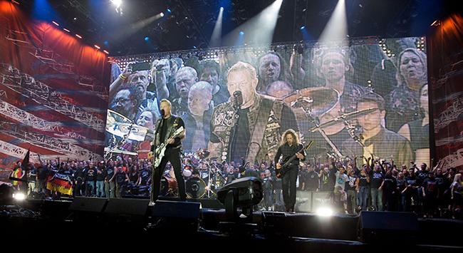 Metallica på scen med vad som kan se ut som en jättekör – men som bara är fans som hänger där i bakgrunden. (Foto: Friso Gentsch/EPA/TT)